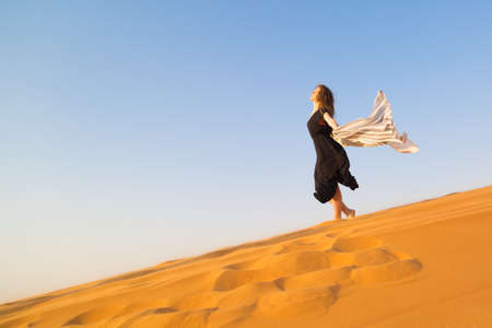 A lonely girl goes down the sand dunes. Caucasian woman in a black dress descends from a mountain in the desert,