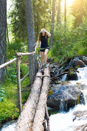 The girl crosses the stream on the fallen logs. A young beautiful tourist walks along boards through a stormy mountain stream Archivio Fotografico
