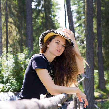 A young girl stands in the forest with a hat on her head. A beautiful young girl holds a hat with one hand, smiles, stands in nature Archivio Fotografico