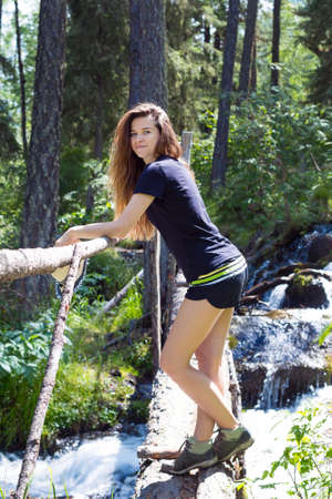 A sporty slender woman of 25-30 years old in sports shorts stands in forest