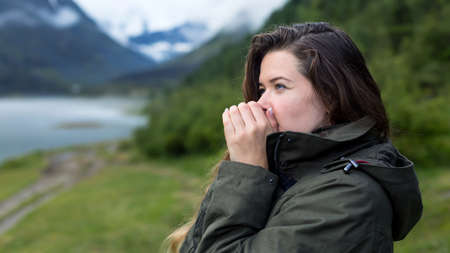 A woman warms her hands with warm breath on a cold morning. Girl tourist blows on her hands warming them on cold morning in the mountains Archivio Fotografico