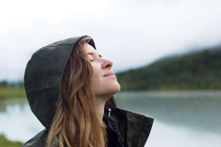 Portrait of a woman in a hood, close-up. Young beautiful woman tourist in a warm jacket and a hood on her head against the backdrop of mountains. Archivio Fotografico
