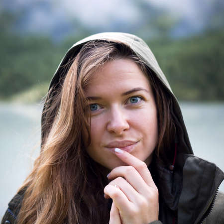 Portrait of young woman in a hood, brings her fingers to her lips. Close-up. Portrait of a girl with fingers near lips, face.
