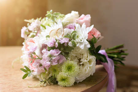 Wedding rings lie on the petals of a flower bridal bouquet