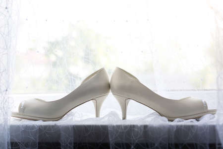 The brides shoes are on the curtain by the window Archivio Fotografico