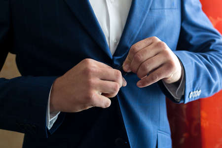 A man fastens a button of his jacket on his stomach Archivio Fotografico