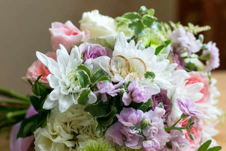 Wedding rings lie on the petals of a flower bridal bouquet.