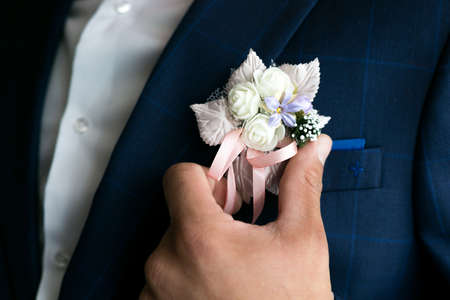Male hand straightens the boutonniere on the groom's suit.
