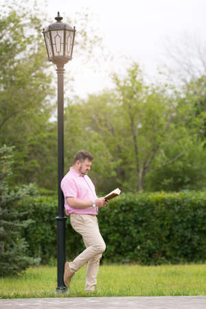 A man in a pink shirt with a book in his hands stands near a lighting pole in a park. Archivio Fotografico