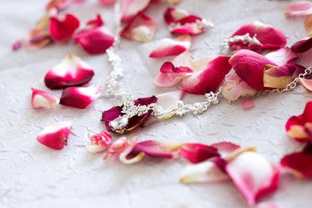 Decorations for the bride are spread among rose petals. Archivio Fotografico