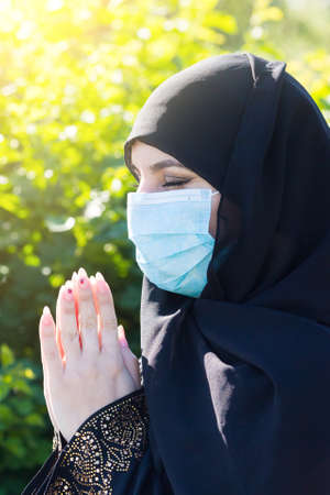Muslim girl in a protective medical mask prays to God during self-isolation and viral quarantine.