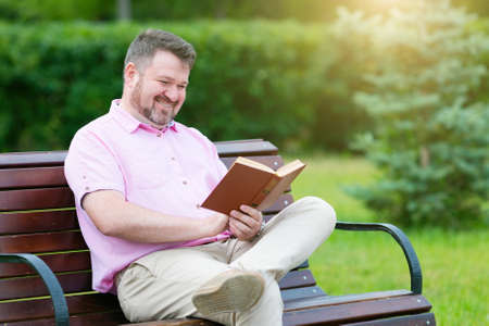 An adult man with a short beard in summer clothes is reading a book while sitting on a bench in the park.
