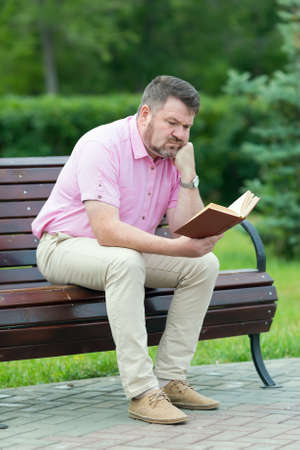 An adult man with short beard in summer clothes is reading a book while sitting on a bench in the park, Archivio Fotografico