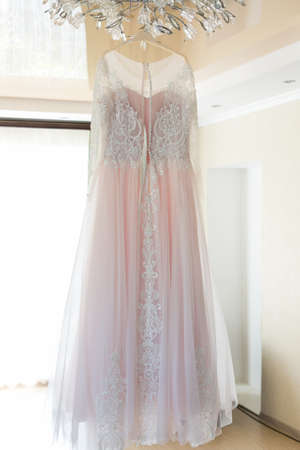 White bride dress hanging on a chandelier in the room.