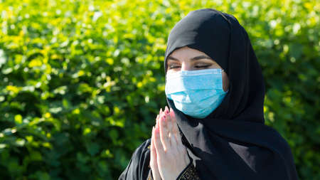 Muslim girl in a protective medical mask prays to God. Muslim girl in a protective medical mask prays to God during self-isolation and viral quarantine