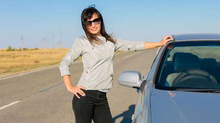 young brunette woman in black glasses stands near her car on an empty road.
