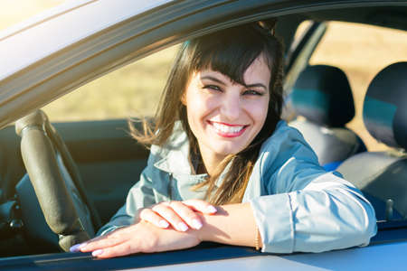 Happy young girl driving a car smiling broadly.