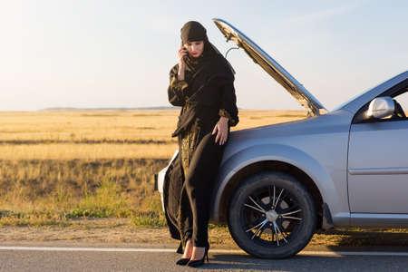 Muslim woman calling help phone near open hood of car.