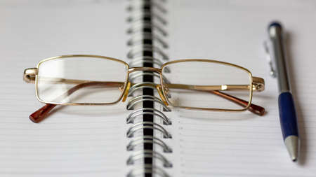 Glasses and a pen on an open notebook Stock Photo