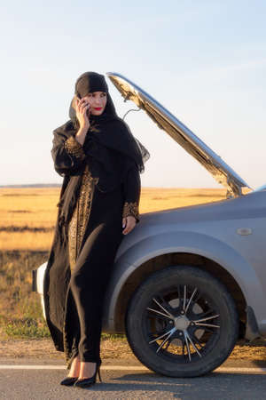 Portrait of a muslim woman calling on the phone near the car.