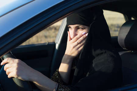 Woman driver scared while driving covered her mouth with her hand.,