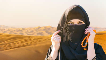 Muslim woman in the desert sands Close-up.