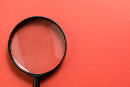 Magnifying glass on red background. Copy space Standard-Bild