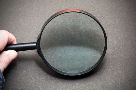 Magnifying glass on a black background. Hand with magnifying glass. Standard-Bild
