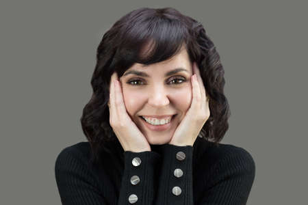 Adult woman in black sweater with short hair. Open wide smile