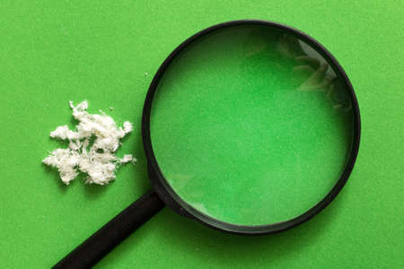 Magnifying glass on a green background next to the asbestos fiber.