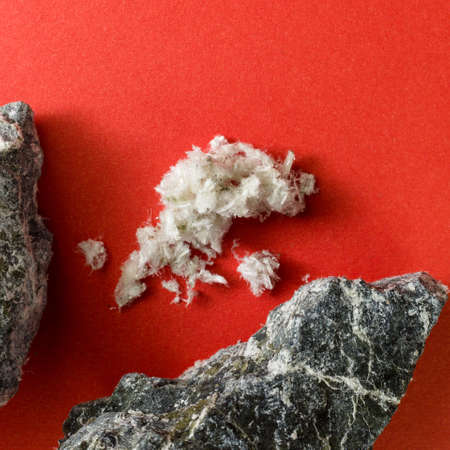 Asbestos fiber on a red background next to mineral stones. Standard-Bild