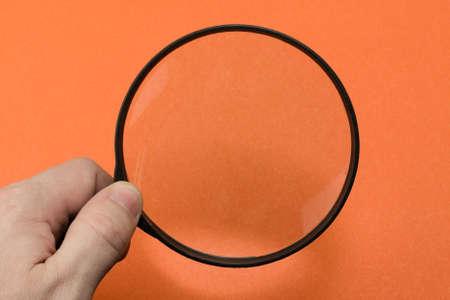 Hand with magnifying glass on orange background.