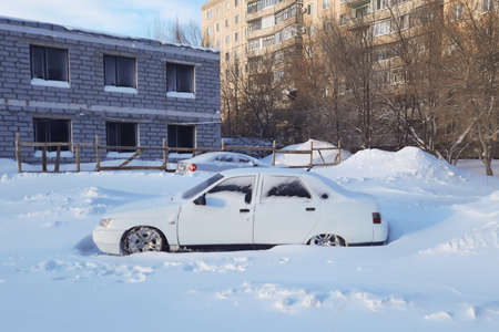 Snow covered white car with low ground clearance.,