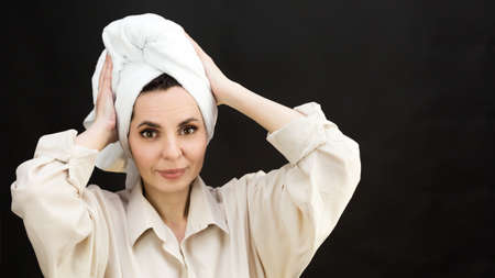 Cheerful adult woman with towel head after shower on black background.