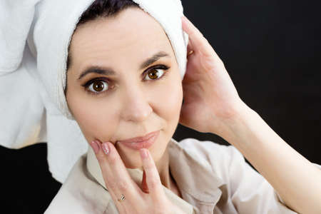 Cheerful adult woman with towel on head after shower on black background. Standard-Bild