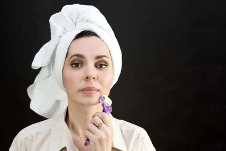 An adult woman smoothes wrinkles on her face after a bath.