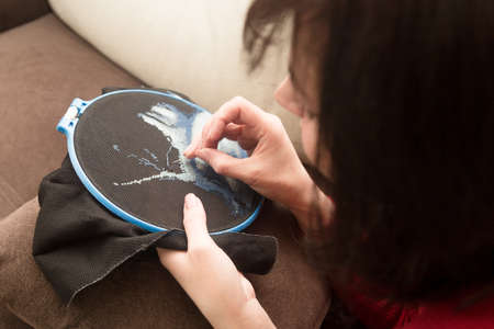 Woman embroiders a cross-stitch image on fabric.