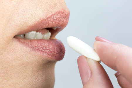 Man brings chewing gum to his mouth, fingers and lips close-up.