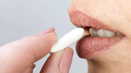 Man brings chewing gum to his mouth fingers and lips close up.