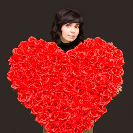 Beautiful brunette with a large bouquet flowers in the shape of a heart.