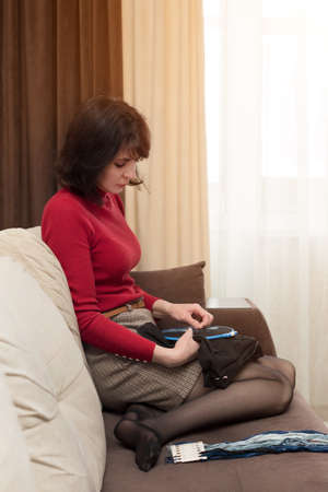 Woman in red clothes sitting on couch is embroidering a picture in a cross.