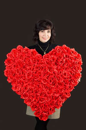 Woman with a padark for Valentine's day, a large bouquet of roses heart. Standard-Bild