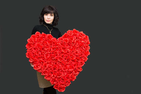 Woman with a padark for Valentine's day large bouquet of roses heart.