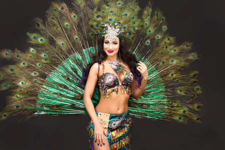 Woman oriental dancer peacock feather costume. Black background