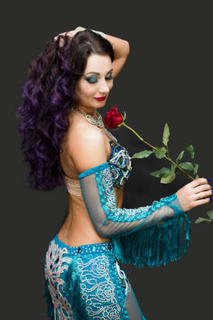 Adult woman dancer in a blue suit with rose in her hands.