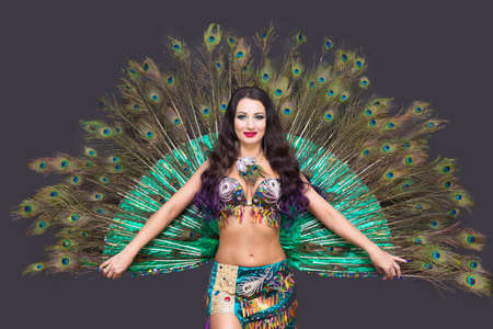 Dancer holds peacock feathers in her hands, black background.