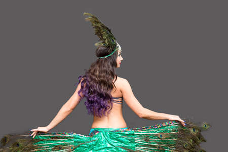 Dancer holds peacock feathers in her hands, black background view from the back.