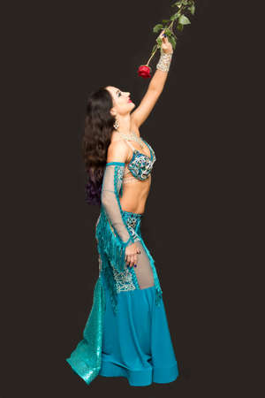 Young woman dancer holding a red rose in her hands.