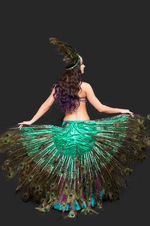Dancer holds peacock feathers in her hands black background view from the back.