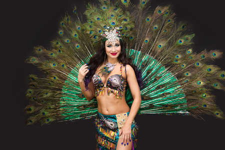 National dancer in a luxurious outfit of bird feathers on a black background, isolated.